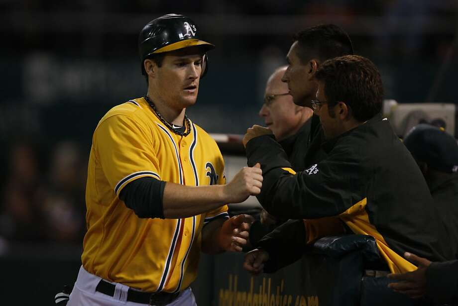 Oakland player Josh Willingham is congratulated by his team after scoring the first run of the night for the Oakland Athletics during the Oakland game against the Texas Rangers in Oakland Calif.,  on August 11, 2011. Photo: Audrey Whitmeyer-Weathers, The Chronicle