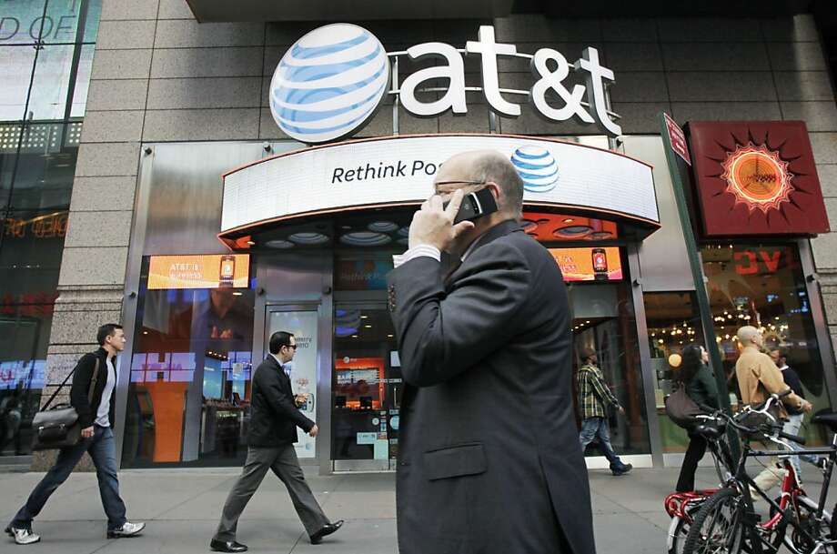 In this Oct. 18, 2011 photo, a man using a cell phone passes an AT&T store, in New York.   AT&T Inc. on Thursday, Oct. 20, 2011,  reported a decline in the number of iPhones activated in its latest quarter, as buyers waited for the new model. ((AP Photo/Mark Lennihan)  Ran on: 11-01-2011 AT&T requires two-year agreements for phones with Long-Term Evolution. Photo: Mark Lennihan, Associated Press