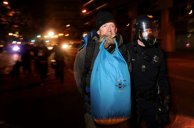 An Occupy Oakland camper carries belonging in his teeth as he's arrested from the group's city hall encampment on Tuesday, Oct. 25, 2011, in Oakland, Calif. Police descended on Occupy Oakland's two camps overnight flattening tents and arresting protesters. Photo: Noah Berger, Special To The Chronicle