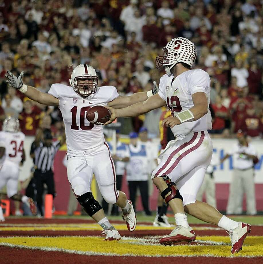 Stanford quarterback Andrew Luck, center, and fullback Geoff Meinken (10) celebrate after Luck scored a touchdown during the second half of an NCAA college football game in Los Angeles, Saturday, Oct. 29, 2011. Stanford won 56-48 in overtime. (AP Photo/Jae C. Hong)  Ran on: 10-30-2011 Andrew Luck had his tough moments, but he ran for a touchdown in the second half and threw for three in the triple-overtime win against USC. Ran on: 10-30-2011 Andrew Luck had his tough moments, but he ran for a touchdown in the second half and threw for three in the triple-overtime win against USC. Ran on: 10-30-2011 Andrew Luck had his tough moments, but he ran for a touchdown in the second half and threw for three in the triple-overtime win against USC. Ran on: 10-30-2011 Andrew Luck had his tough moments, but he ran for a touchdown in the second half and threw for three in the triple-overtime win against USC. Photo: Jae Hong, AP