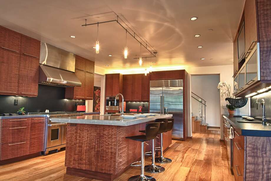 Custom cabinetry and stainless steel appliances are showcased in the kitchen. Photo: Photos By Gary Dangerfield