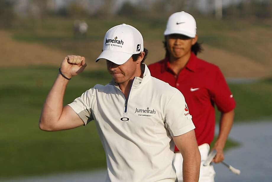Rory McIlroy of Northern Ireland celebrates on the 18th green after winning the Lake Malaren Shanghai Masters golf tournament, with Anthony Kim of the United States in the back watching, in Shanghai, China, Sunday, Oct. 30, 2011. U.S. Open champion McIlroy won $2 million in the Shanghai Masters on Sunday, beating Kim with a par on the first hole of a playoff. (AP Photo/Alexander F. Yuan)  Ran on: 10-31-2011 Rory McIlroy beat Anthony Kim (background) by a foot Sunday in Shanghai. Ran on: 10-31-2011 Rory McIlroy beat Anthony Kim (background) by a foot Sunday in Shanghai. Photo: Alexander F. Yuan, AP