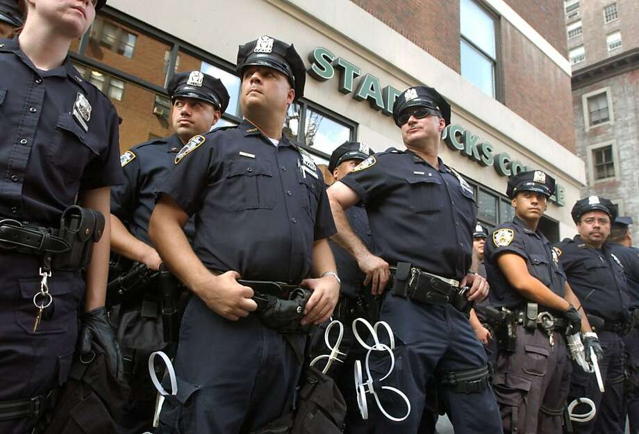 New York police form a barrier in front of a during a Starbucks coffee shop during a demonstration against Starbucks' workplace practices and the Bush administration's alleged support for the chain's anti-union practices in New York Saturday Aug. 28, 2004. The Republican National Convention is scheduled to begin in New York on Monday.  (AP Photo/Jacqueline Larma)  Ran on: 08-29-2004 A worker on a lift checks the convention stage against the backdrop of the giant screen at Madison Square Garden.  Ran on: 08-29-2004 A worker on a lift checks the convention stage against the backdrop of the giant screen at Madison Square Garden.  Ran on: 10-30-2011 The thick blue line: New York City beefed up its police force and rethought strategies. Ran on: 10-30-2011 The thick blue line: New York City beefed up its police force and rethought strategies. Ran on: 10-30-2011 The thick blue line: New York City beefed up its police force and rethought strategies. Ran on: 10-30-2011 The thick blue line: New York City beefed up its police force and rethought strategies. Photo: Jacqueline Larma, Associated Press