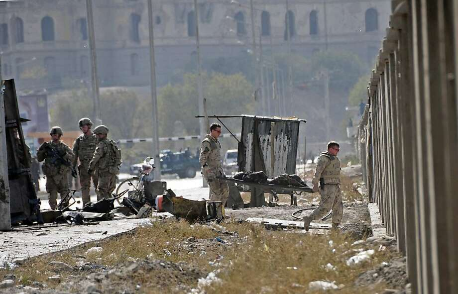 NATO forces carry a corpse from the site of a suicide attack near Darul Aman Palace (back) in Kabul on October 29, 2011. At least 14 people, mostly foreign forces, were killed when a Taliban car bomber struck a US-run NATO convoy travelling through the Afghan capital Kabul. The attacker detonated his Toyota Sedan car at 11:20 am (0650 GMT) in the southwest of the city, and at least ten foreign forces, three civilians and a policeman were among the casualties, police and Western officials said. AFP PHOTO / STR (Photo credit should read STR/AFP/Getty Images) Photo: Str, AFP/Getty Images
