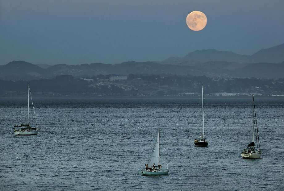 The crew aboard a sailboat tend to their vessell as the moon rises over San Francisco Bay as seen from China Camp State Park on Saturday August 13, 2011, in San Rafael, Ca. Photo: Michael Macor, The Chronicle