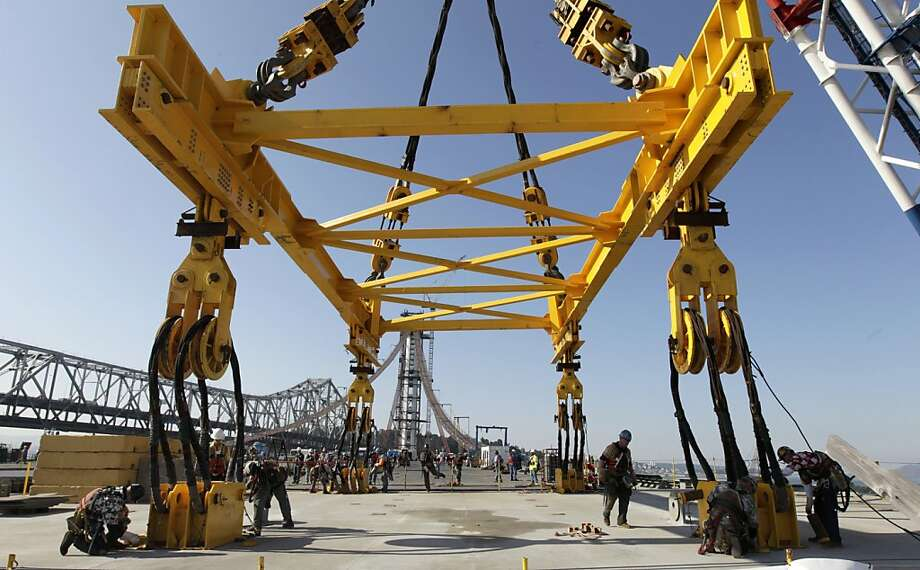 Ironworkers remove huge cables suspended from the Left Coast Lifter floating crane after the final section of the new eastern span of the Bay Bridge was lowered into place in San Francisco, Calif. on Friday, Oct. 28, 2011. Photo: Paul Chinn, The Chronicle