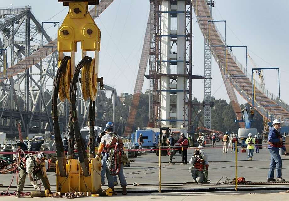 Ironworkers remove huge cables suspended from the Left Coast Lifter floating crane after the final section of the new eastern span of the Bay Bridge is lowered into place in San Francisco, Calif. on Friday, Oct. 28, 2011. Photo: Paul Chinn, The Chronicle