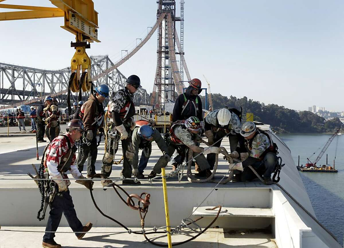 Ironworkers pull on a rope line after the final section of the new eastern span of the Bay Bridge is lowered into place in San Francisco, Calif. on Friday, Oct. 28, 2011.