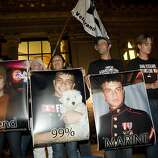 Friends and family of Scott Olsen, the Iraq War veteran who was injured in Tuesday's protest, hold pictures of Olsen during a vigil outside of Oakland City Hall at the Occupy Oakland camp in Frank Ogawa on Thursday, October 27, 2011 in Oakland, Calif. Ran on: 10-28-2011 Friends and relatives hold pictures of Scott Olsen during a vigil near Oakland City Hall. Ran on: 10-28-2011 Friends and relatives hold pictures of Scott Olsen during a vigil near Oakland City Hall.