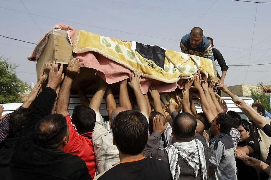 Friends and relatives load the coffin of a man killed in a bomb attack at a music store in Baghdad, Iraq, Friday, Oct. 28, 2011. On Thursday twin bombing  killed and wounded scores of people in a Shiite neighborhood in Baghdad the deadliest attack to rock Iraq since President Barack Obama declared the full withdrawal of U.S. forces at the end of the year. (AP Photo/Karim Kadim) Ran on: 10-29-2011 Friends and relatives load the coffin of a man killed in a bomb attack at a music store in Baghdad. Photo: Karim Kadim, AP