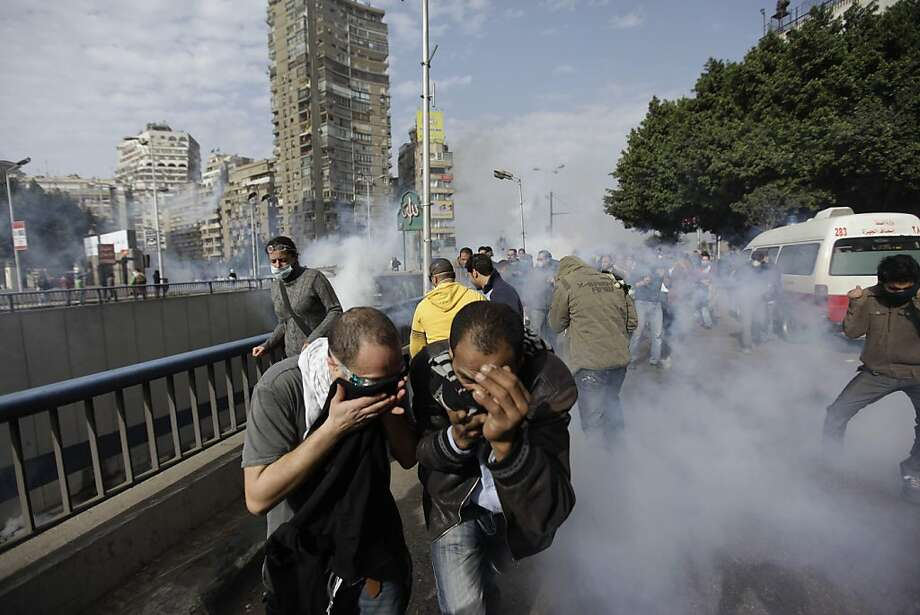 Egyptian anti-government activists run for a cover from the tear gaz during clashes with the riot- police in Cairo, Egypt, Friday, Jan. 28, 2011. Egyptian activists protested for a fourth day as social networking sites called for a mass rally in the capital Cairo after Friday prayers, keeping up the momentum of the country's largest anti-government protests in years. (AP Photo/Ben Curtis) Ran on: 01-29-2011 Anti-government activists run for cover from tear gas during clashes with riot police in Cairo Friday. Battling police with stones and firebombs, protesters burned down the ruling party headquarters and defied a nighttime curfew. A3  In Business, high-tech leaders respond to the government's Internet shutdown. D1 Ran on: 01-29-2011 Anti-government activists run for cover from tear gas during clashes with riot police in Cairo Friday. Battling police with stones and firebombs, protesters burned down the ruling party headquarters and defied a nighttime curfew. A4  In Business, high-tech leaders respond to the government's Internet shutdown. D1 Photo: Ben Curtis, AP
