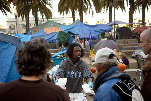 Emmanuel Bereket, of San Francisco, hands out donated sandwiches to residents of the Occupy SF camp in Justin Herman Plaza on Thursday, October 27, 2011 in San Francisco, Calif. Photo: Beck Diefenbach, Special To The Chronicle
