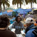 Emmanuel Bereket, of San Francisco, hands out donated sandwiches to residents of the Occupy SF camp in Justin Herman Plaza on Thursday, October 27, 2011 in San Francisco, Calif.