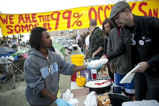 Emmanuel Bereket (left), of San Francisco, hands out donated sandwiches to residents of the Occupy SF camp in Justin Herman Plaza on Thursday, October 27, 2011 in San Francisco, Calif. Photo: Beck Diefenbach, Special To The Chronicle