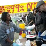 Emmanuel Bereket (left), of San Francisco, hands out donated sandwiches to residents of the Occupy SF camp in Justin Herman Plaza on Thursday, October 27, 2011 in San Francisco, Calif.