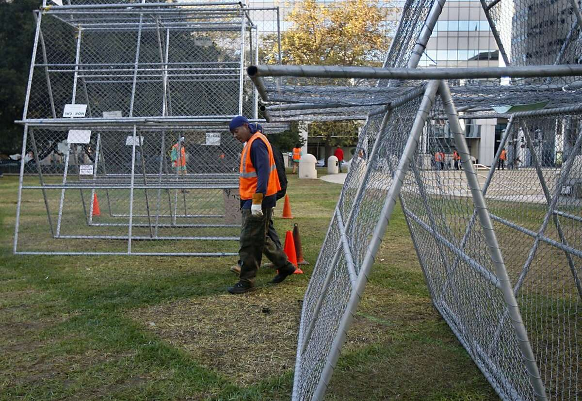 A Department of Public Works crew search the lawn for tent stakes at Frank Ogawa Plaza in Oakland, Calif. on Thursday, Oct. 27, 2011 near structures created by protesters using fencing erected after a police raid dismantled the Occupy Oakland encampment before dawn on Tuesday. Demonstrators have vowed to reoccupy the park. Ran on: 10-28-2011 A member of a Department of Public Works crew searches the lawn for tent stakes at Frank Ogawa Plaza in Oakland. Ran on: 10-28-2011 A member of a Department of Public Works crew searches the lawn for tent stakes at Frank Ogawa Plaza in Oakland.