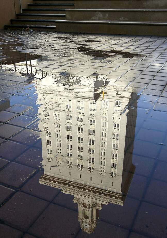 Oakland City Hall is reflected in a puddle after a power washer was used to clean Frank Ogawa Plaza in Oakland, Calif. on Thursday, Oct. 27, 2011. A police raid dismantled the Occupy Oakland encampment before dawn on Tuesday and protesters have vowed to reoccupy the park. Photo: Paul Chinn, The Chronicle
