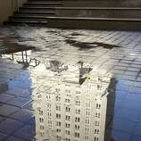 Oakland City Hall is reflected in a puddle after a power washer was used to clean Frank Ogawa Plaza in Oakland, Calif. on Thursday, Oct. 27, 2011. A police raid dismantled the Occupy Oakland encampment before dawn on Tuesday and protesters have vowed to reoccupy the park.