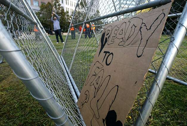 Occupy Oakland protesters tore down a fence blocking entry into Frank Ogawa Plaza and stacked them into triangular structures in Oakland, Calif. on Thursday, Oct. 27, 2011. A police raid dismantled the Occupy Oakland encampment before dawn on Tuesday and demonstrators have vowed to reoccupy the park. Photo: Paul Chinn, The Chronicle