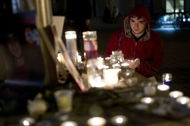 E. J. Fox, of Oakland, light candles in honor of Scott Olsen, the Iraq War veteran who was injured in Tuesday's protest, following a vigil outside of Oakland City Hall at the Occupy Oakland camp in Frank Ogawa Square on Thursday, October 27, 2011 in Oakland, Calif. Photo: Beck Diefenbach, Special To The Chronicle