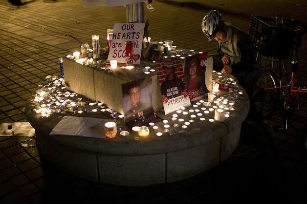 Chimy Lee, of Berkeley, light candles in honor of Scott Olsen, the Iraq War veteran who was injured in Tuesday's protest, following a vigil outside of Oakland City Hall at the Occupy Oakland camp in Frank Ogawa Square on Thursday, October 27, 2011 in Oakland, Calif. Photo: Beck Diefenbach, Special To The Chronicle
