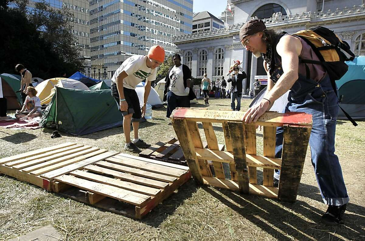 Ian Murdock, (left) and Daniel Kaiya begins to reconstruct a pallet pathway as the Occupy Oakland encampment continues to be put back together and grow in Frank Ogawa Plaza in front of city hall in Oakland, Ca. on Friday October 28, 2011.
