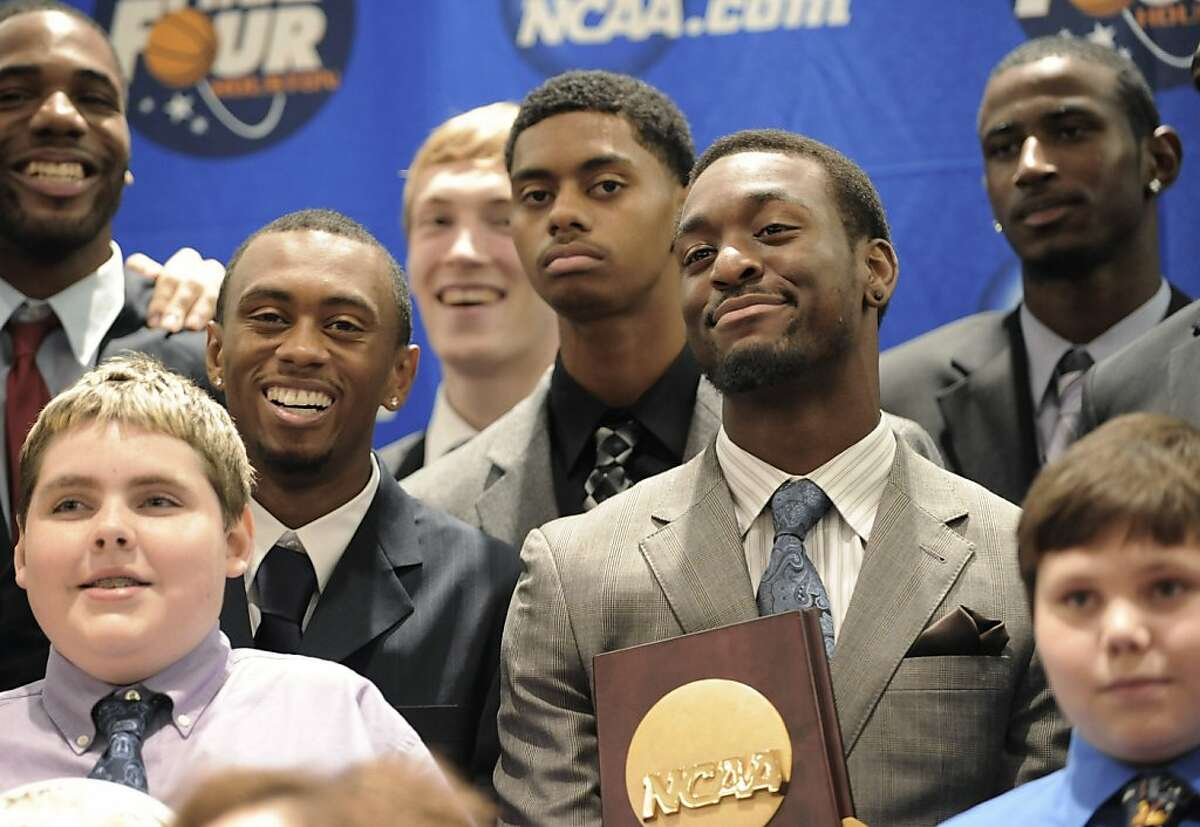 Former Connecticut basketball player Kemba Walker holds the NCAA championship trophy as he stands with teammates and children from Make-A-Wish Foundation during a dinner at which members of the 2010-11 team received their championship rings, in Hartford, Conn., Thursday, Oct. 6, 2011. (AP Photo/Jessica Hill)