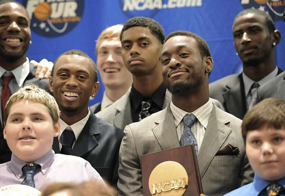 Former Connecticut basketball player Kemba Walker holds the NCAA championship trophy as he stands with teammates and children from Make-A-Wish Foundation during a dinner at which members of the 2010-11 team received their championship rings, in Hartford, Conn., Thursday, Oct. 6, 2011. (AP Photo/Jessica Hill) Photo: Jessica Hill, AP