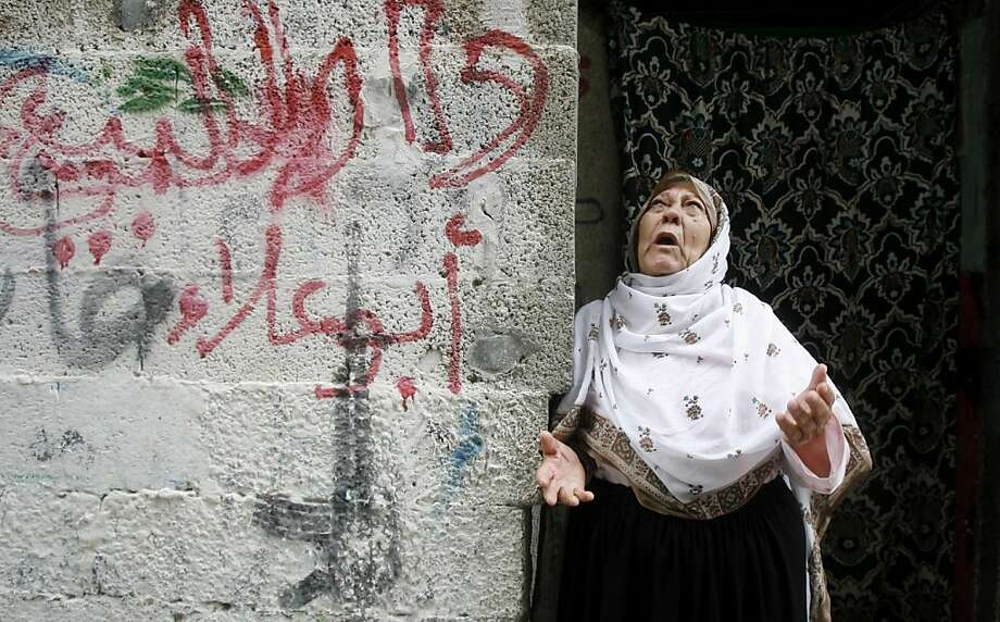 """A Palestinian woman reacts during the funeral of Ismalic Jihad militant of Ahmed al-Sheikh Khalil and other two militants, in Rafah, southern Gaza Strip, Sunday, Oct. 30, 2011. Nine militants and an Israeli civilian were killed in some of the worst violence in the area in months. The exchange of fire continued overnight, with Palestinians firing 10 rockets into Israel in the early hours of the morning, and Israeli aircraft targeting six militant sites in Gaza, the military said. Arabic on wall reads: """"House for sale, Abu Ala"""". (AP Photo/Eyad Baba) Photo: Eyad Baba, AP"""