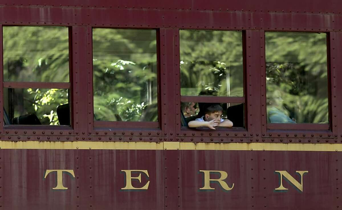 A young boy passenger of the Skunk Train waves to the kids at the SF Boys and Girls club, Friday July 1, 2011, as it passes through Camp Mendocino site, in Willits, Calif.