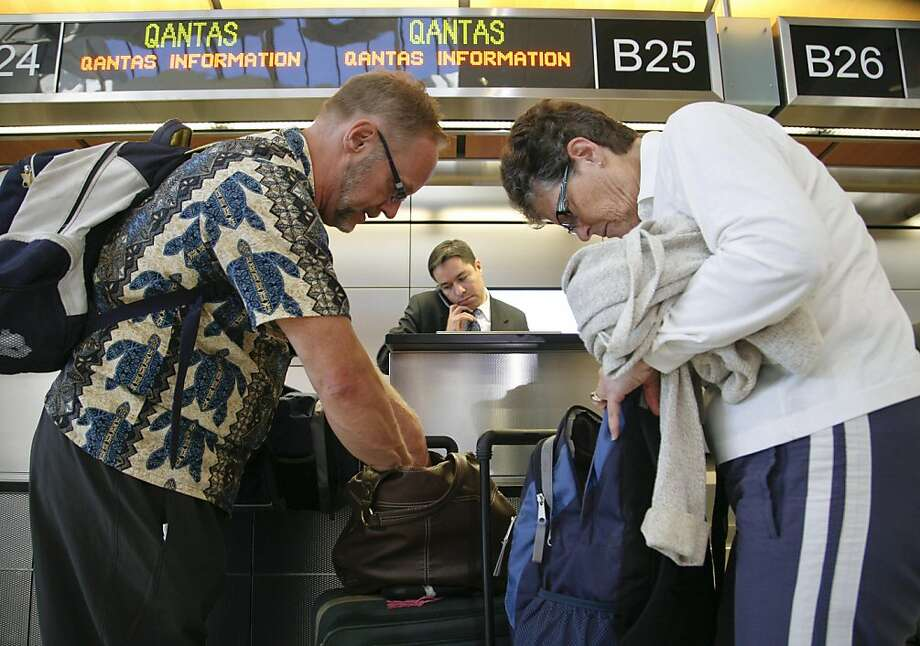 CORRECTS DATE TO OCT. 29, 2011 - Don, left, and Derry Dunsmore of Mine Hill, New Jersey wait at the Quantas counter as they try to reschedule their canceled flight to Sydney at the at Los Angeles International Airport in Los Angeles Saturday, Oct.  29, 2011. Qantas Airways grounded its global fleet Saturday, suddenly locking out striking workers after weeks of flight disruptions. (AP Photo/Jason Redmond) Ran on: 10-30-2011 Don and Derry Dunsmore of New Jersey wait at the Qantas counter at Los Angeles International Airport, trying to reschedule their canceled flight to Sydney. Ran on: 10-30-2011 Don and Derry Dunsmore of New Jersey wait at the Qantas counter at Los Angeles International Airport, trying to reschedule their canceled flight to Sydney. Photo: Jason Redmond, AP