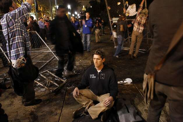An Occupy Oakland protester (declined to give his name) meditates as others remove chain link fence from where the group's camp had previously been located. Occupy Oakland protesters returned to Frank Ogawa Plaza in Oakland, Calif, on Wednesday, October 26, 2011. . Photo: Carlos Avila Gonzalez, The Chronicle