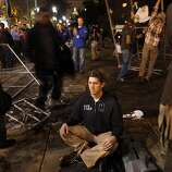 An Occupy Oakland protester (declined to give his name) meditates as others remove chain link fence from where the group's camp had previously been located. Occupy Oakland protesters returned to Frank Ogawa Plaza in Oakland, Calif, on Wednesday, October 26, 2011. .