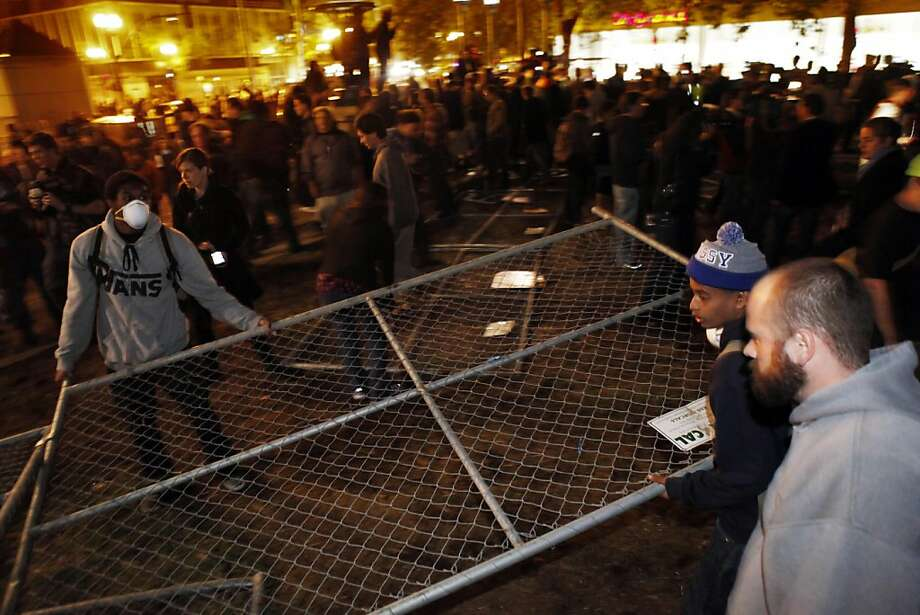 An Occupy Oakland protester removes a section of chain link fence from where the group's camp had previously been located. Occupy Oakland protesters returned to Frank Ogawa Plaza in Oakland, Calif, on Wednesday, October 26, 2011. . Photo: Carlos Avila Gonzalez, The Chronicle