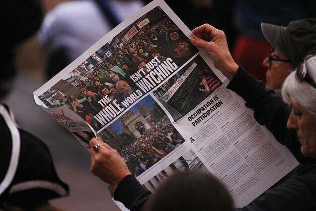 An Occupy Oakland protestor reads a newspaper during a General Assembly meeting at Frank Ogawa Plaza in front of City Hall in Oakland, Calif., on Wednesday, Oct. 27, 2011. Photo: Dylan Entelis, The Chronicle