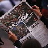 An Occupy Oakland protestor reads a newspaper during a General Assembly meeting at Frank Ogawa Plaza in front of City Hall in Oakland, Calif., on Wednesday, Oct. 27, 2011.