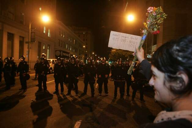 An Occupy Oakland protester shows a sign and bouquet of flowers to an Oakland Police line on a street just off Broadway on Wednesday, Oct. 26, 2011, in Oakland, Calif. Photo: Mathew Sumner, Special To The Chronicle