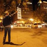 Theresa Wilson of Concord rallies support from passing motorists on 14th Street as Occupy Oakland protesters returned to Frank Ogawa Plaza in Oakland, Calif, on Wednesday, October 26, 2011. .
