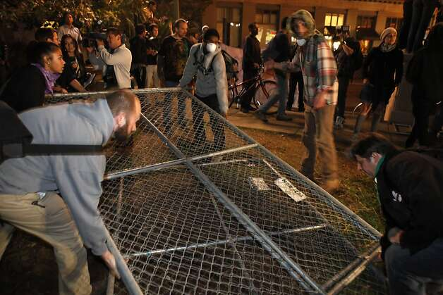 Several Occupy Oakland protesters remove a section of chain link fence from where the group's camp had previously been located. Occupy Oakland protesters returned to Frank Ogawa Plaza in Oakland, Calif, on Wednesday, October 26, 2011. . Photo: Carlos Avila Gonzalez, The Chronicle