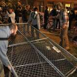 Several Occupy Oakland protesters remove a section of chain link fence from where the group's camp had previously been located. Occupy Oakland protesters returned to Frank Ogawa Plaza in Oakland, Calif, on Wednesday, October 26, 2011. .