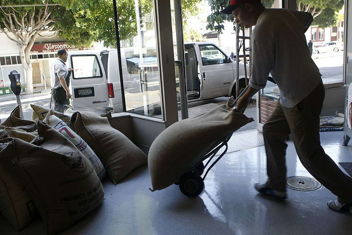 Driver Carlos Bermudez moving bags of coffee beans from the truck to Graffeo Coffee roasting company in the North Beach in San Francisco, Calif., on Monday, September 26, 2011. The company has been family run and owned since 1935.