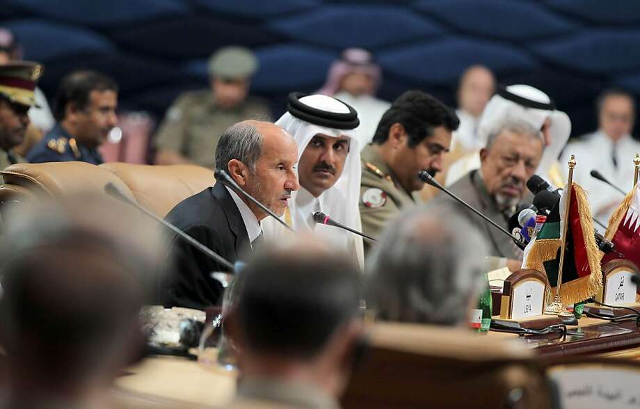 """Qatari Crown Prince Sheikh Tamim bin Hamad al-Thani  (C) listens to Libya's National Transitional Council (NTC) chairman Mustafa Abdel Jalil (L) as he addresses the """"Friends of Libya"""" group meeting held in Doha, Qatar on October 26, 2011 to discuss the future of the country after Moamer Kadhafi was buried in secret. The  AFP PHOTO / KARIM SAHIB (Photo credit should read KARIM SAHIB/AFP/Getty Images) Photo: Karim Sahib, AFP/Getty Images"""