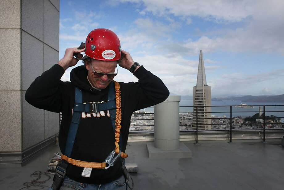 Jim Phelan gears up with a harness and a helmet before starting his climb at 345 California Center. He says it his quick and experience that are his most valuable tools. Photo: Mike Kepka, The Chronicle