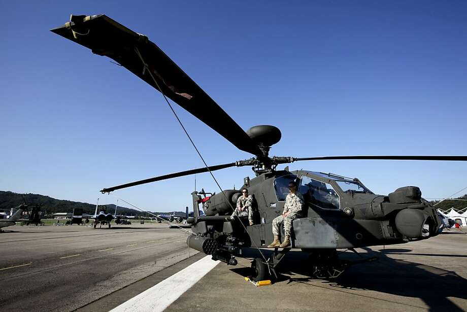 United States army soldiers sit on a AH-64D Longbow Apache helicopter manufactured by Boeing Co. during a media preview of the Seoul International Aerospace & Defense Exhibition 2011 at Seoul Airport in Seongnam, South Korea, on Monday, Oct. 17, 2011. Armored vehicles, trainer jets and weapons will be on display this week at South Korea's biggest aerospace and defense exhibition, as the nation works to triple annual military exports by the end of the decade. Photographer: SeongJoon Cho/Bloomberg Photo: SeongJoon Cho, Bloomberg