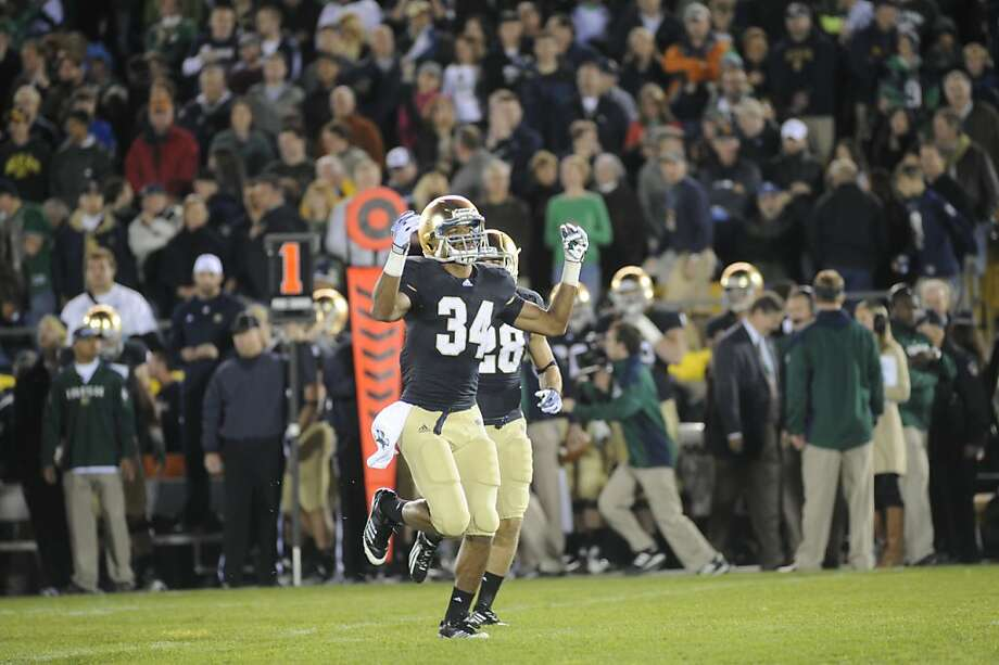 Notre Dame lineman Andrew Nuss displays the new helmet that Notre Dame is wearing for the first time in an NCAA college football game in South Bend. Ind., Saturday, Oct. 22, 2011.  (AP Photo/Joe Raymond)Notre Dame kick off returner George Atkinson III encourages the crowd during the first half of an NCAA college football game in South Bend. Ind., Saturday, Oct. 22, 2011.  (AP Photo/Joe Raymond) Photo: Joe Raymond, AP