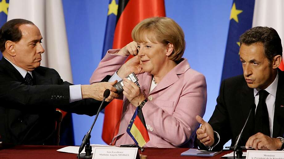 """FILE - In this Saturday Oct. 4, 2008 file photo, French President Nicolas Sarkozy, right, speaks as German Chancellor Angela Merkel, center, receives help with her earphone from Italian Prime Minister Silvio Berlusconi during a media conference at an emergency financial summit at the Elysee Palace in Paris. Berlusconi lashed out Monday, Oct. 24, 2011, at his German and French counterparts who have demanded Italy introduce tough new measures to spur economic growth, chiding them for trying to """"give lessons"""" to Rome and insisting Italy's economy was stable. Berlusconi's pointedly critical statement came as he summoned his Cabinet for an emergency meeting to discuss growth measures the European Union has demanded so Italy doesn't get further dragged into Europe's debt crisis. (AP Photo/Virginia Mayo, File) Photo: Virginia Mayo, AP"""