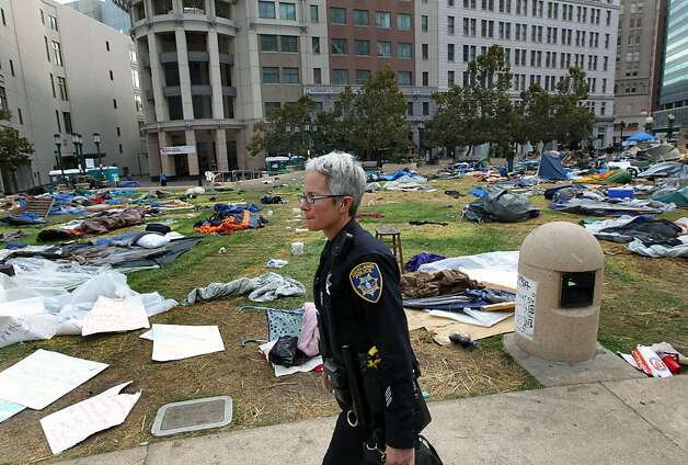 Oakland police officers walk amid possessions left behind by Occupy Oakland protestors across from City Hall Tuesday, Oct. 25, 2011, in Oakland, Calif. Occupy Oakland protestors were evicted from Frank H. Ogawa plaza early this morning. Photo: Lance Iversen, The Chronicle