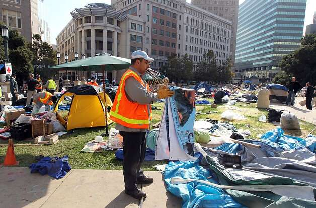 Oakland city employees carefully gather possessions left behind by Occupy Oakland protestors who were evicted from Frank H. Ogawa plaza in front of City Hall Tuesday, Oct. 25, 2011. Photo: Lance Iversen, The Chronicle