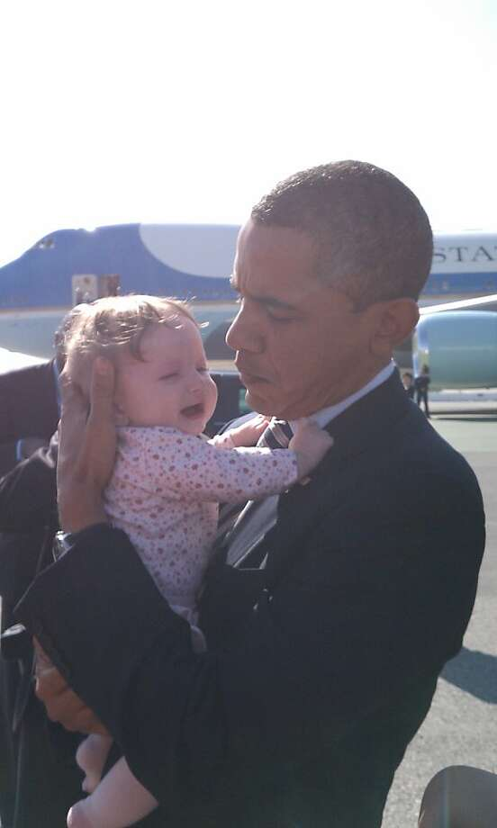President Obama soothes a crying 6-month-old baby, Josie Knight, at San Francisco International Airport on Oct. 25, 2011. Photo: Gina Odom
