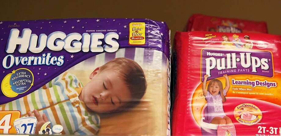 FILE - In this Jan. 10, 2011 file photo, packages of Huggies and Pull-Ups, both Kimberly Clark brands, are displayed at a store in San Francisco. Kimberly-Clark Corp., maker of Kleenex, Huggies and other well-known household brands, said Monday, Oct. 24, 2011, that its net income fell 8 percent in the third quarter because of rising costs. It also cut its revenue outlook and the high end of its earnings outlook. (AP Photo/Jeff Chiu, File)  Ran on: 10-25-2011 The maker of Huggies and Pull-Ups cut its revenue outlook as income fell. Photo: Jeff Chiu, AP